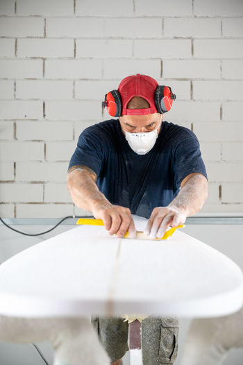 Man working against wall
