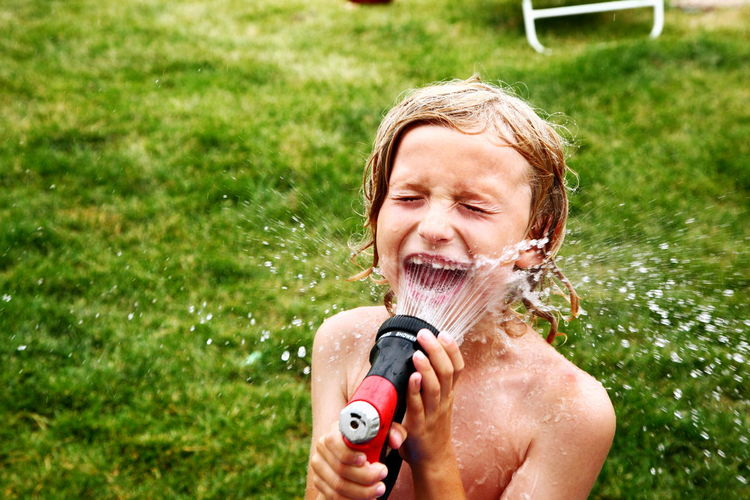 Shirtless Boy Splashing Water From Garden Hose On Face In Back Yard