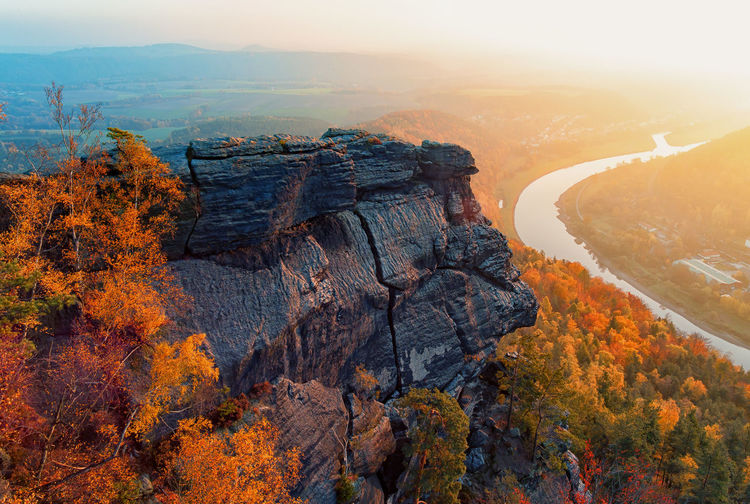 Scenic view of rocky mountain and autumn trees during sunset at saxon switzerland national park
