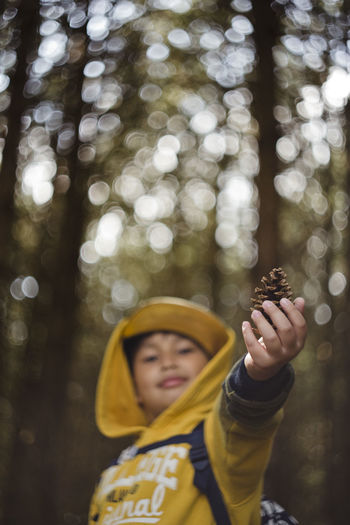 Portrait Of Smiling Boy Holding Pine Cone In Forest
