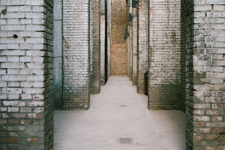 Empty walkway amidst brick walls