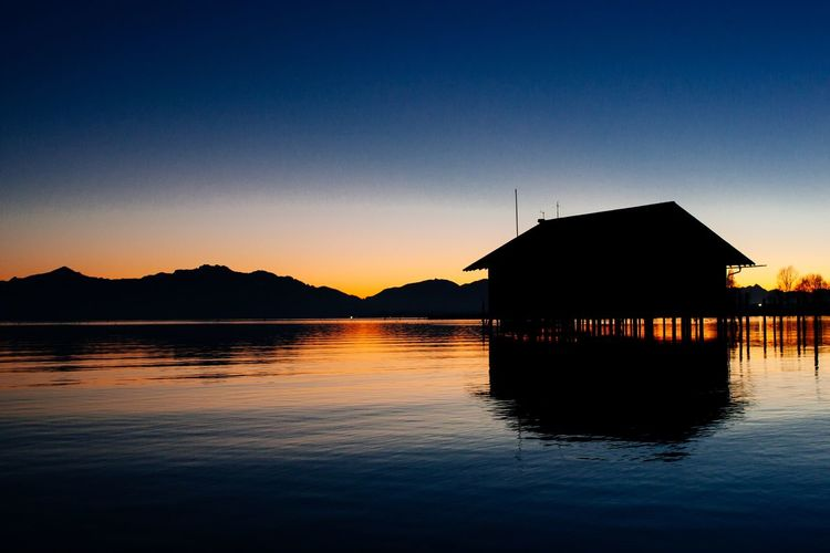 Silhouette House By Lake Against Sky During Sunset