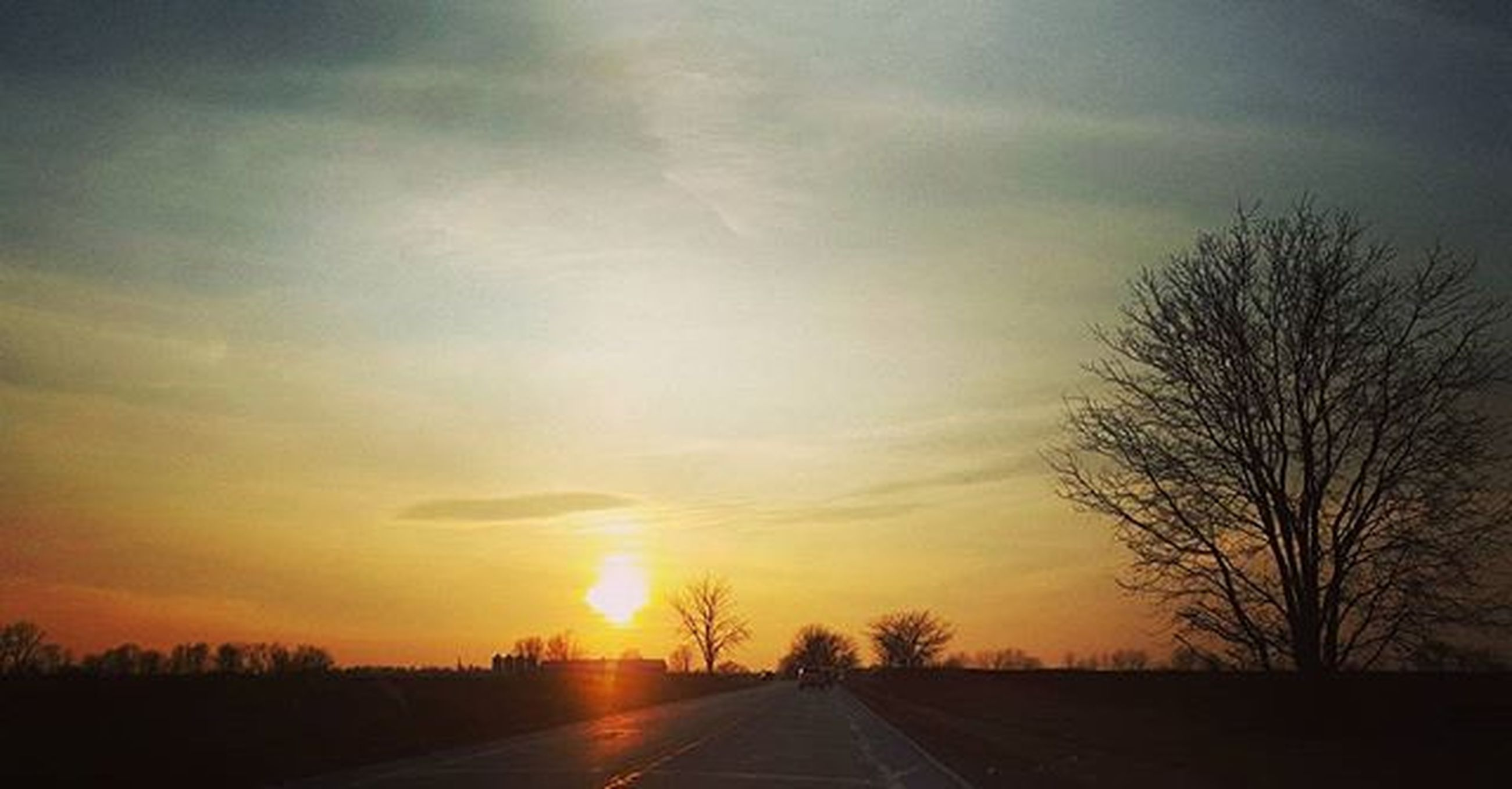 sunset, the way forward, transportation, sky, road, orange color, silhouette, tree, diminishing perspective, tranquility, sun, tranquil scene, vanishing point, scenics, cloud - sky, beauty in nature, landscape, nature, bare tree, country road
