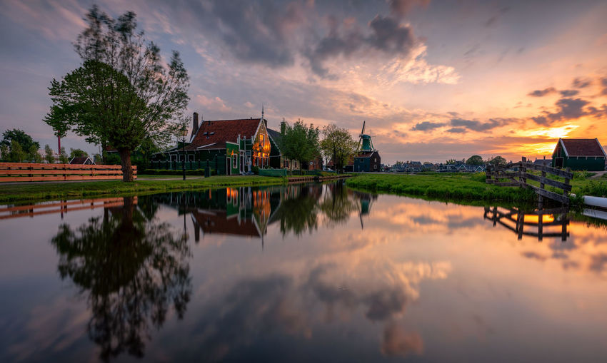 Sunset at The Zaanse Schans, Netherlands Sky Water Cloud - Sky Built Structure Reflection Waterfront Tree Sunset Beauty In Nature No People Place Of Worship Outdoors Holland Netherlands Dutch Landscape Dutch Landscape Nederland Zaandijk Zaanse Schans Zaandam Travel Destinations Tourist Attraction  Tourist Destination Windmill Traditional Windmill Full Frame Reinaroundtheglobe Traditional House Tranquility