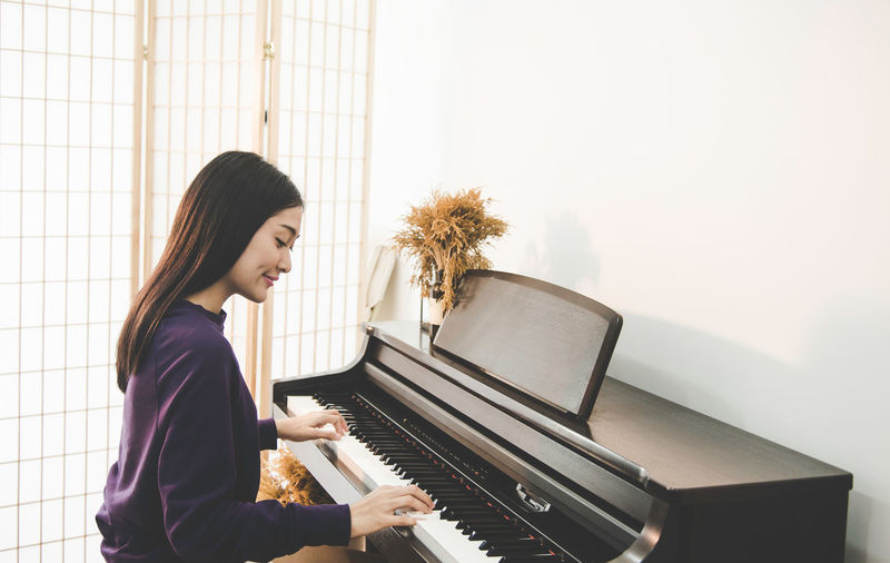 Side view of smiling woman playing piano at home
