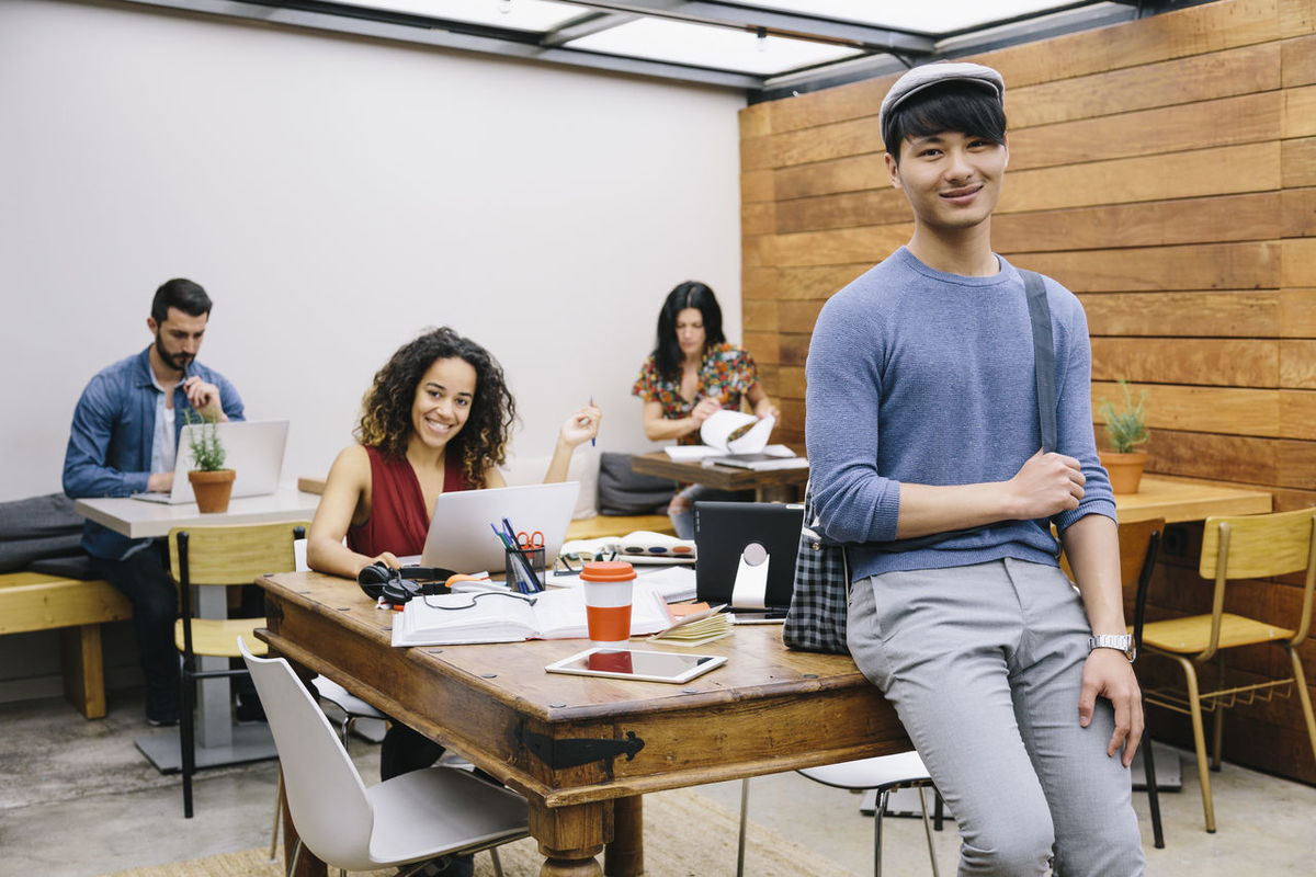 Businessman Casual Clothing Chinese Man Colleagues Coworker Coworking Creative Designer  Laptop Looking At Camera Men Office Portrait Portrait Of A Woman Real People Smile Smiling Startup Student Technologie Technology Wireless Technology Working Young Adult Young Men