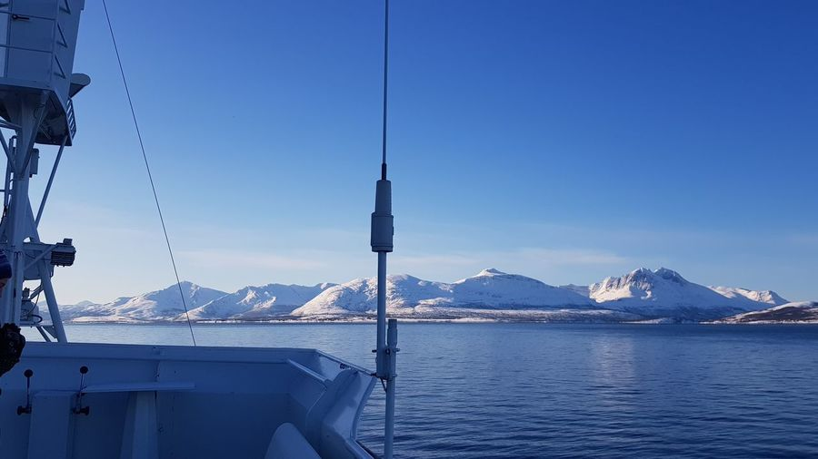 View of snow-capped mountains along a fjord, from a fishing vessel. Antenna - Aerial Biat Sea Water Travel Landscape EyeEm Selects Water Mountain Snow Cold Temperature Clear Sky Winter Sea Glacier Snowcapped Mountain Blue