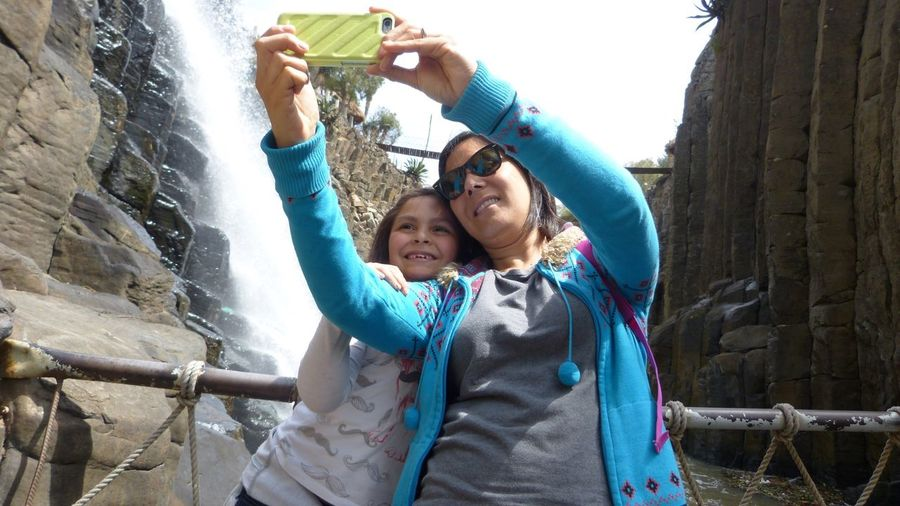 Low angle view of mother taking selfie with daughter standing against waterfall