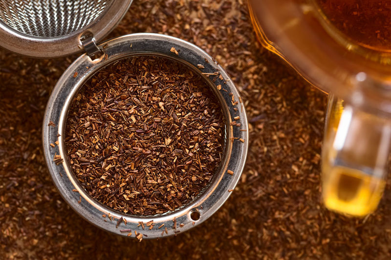 Rooibos herbal tea in strainer with freshly prepared tea on the side, photographed overhead with natural light (Selective Focus, Focus on the top leaves in the strainer) African Beverage Herb Red Tea Close-up Dried Drink Dry Food Food And Drink Herbal Herbal Tea Ingredient Loose Loose Leaf Tea Loose Tea Overhead Red Bush Rooibos Rooibos Tea South African Strainer Tea Leaves Tea Strainer