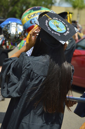 Rear view of woman wearing mortarboard on street