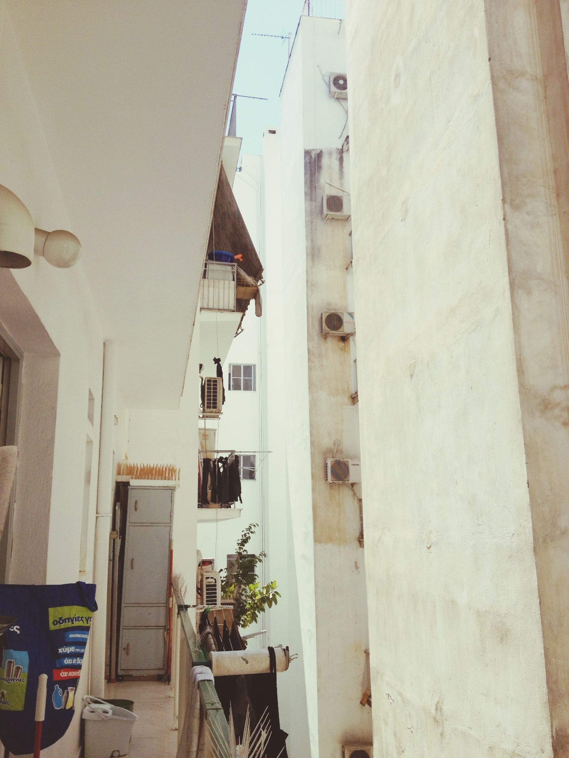 architecture, built structure, building exterior, residential structure, residential building, building, house, window, low angle view, day, no people, city, outdoors, balcony, hanging, sunlight, exterior, town, door, wall - building feature
