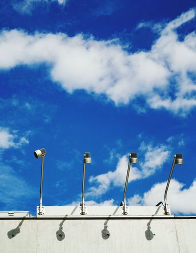 Low angle view of lighting equipment on billboard against blue sky during sunny day