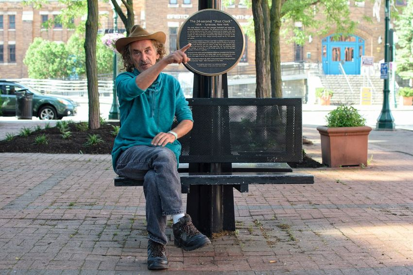 Just Look at the Sign. (release available) Old Man Senior Adult Pointing Directions Cowboy Hat Jeans Urban City Full Length Casual Clothing Bench Park Park Bench Urban Scene Cowboy