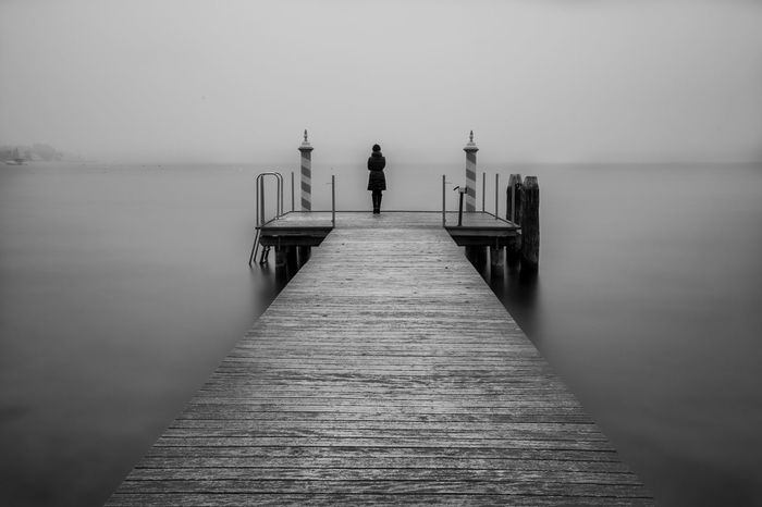 B&W jetty on a lake Blackandwhite Fog Italia Italy Jetty Minimalist Jetty View Lake Lake View Lakescape Lakeside Landscape Longexposure One Man Only One Person Pier Silence Tranquil Scene Tranquility Water The Great Outdoors - 2017 EyeEm Awards