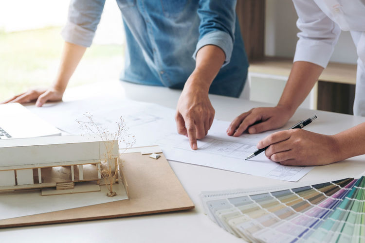 Midsection of engineers drawing blueprint in office
