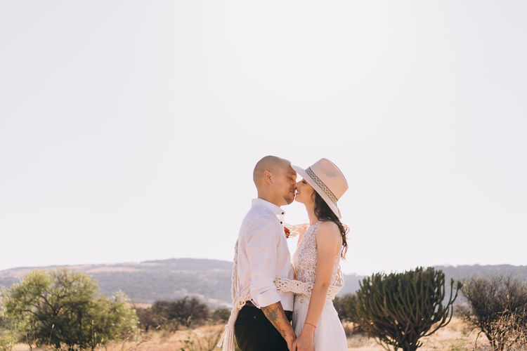 Side view of couple standing against clear sky