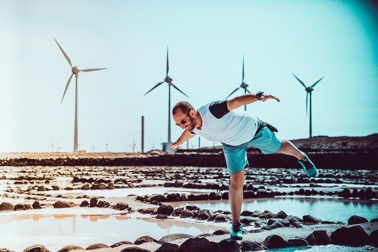 Happy Man With Arms Outstretched Balancing On Rocks Against Windmills