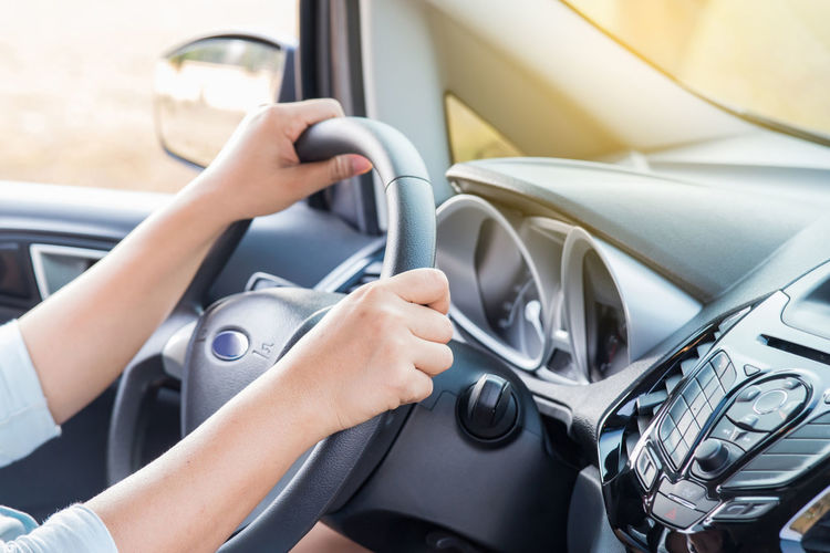 Close-up of hand holding steering wheel in car