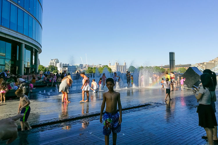 People at swimming pool against clear sky
