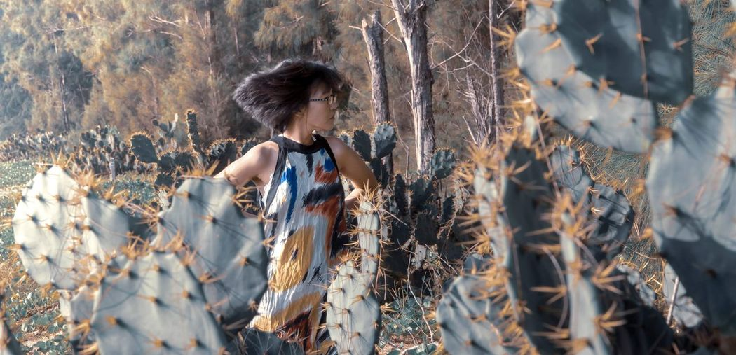 Woman standing by cactus plants in forest