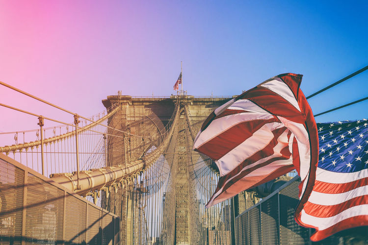 Low Angle View Of American Flag Against Brooklyn Bridge During Sunset