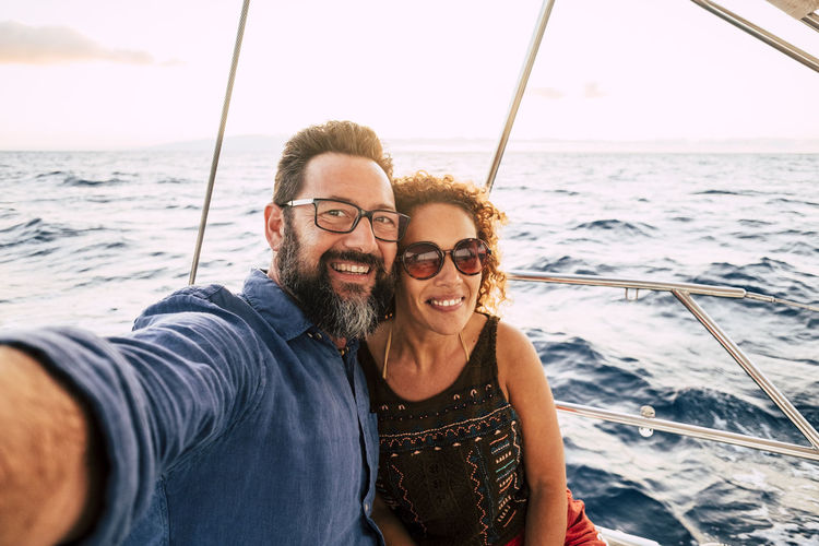 Portrait of smiling couple doing selfie at boat in sea