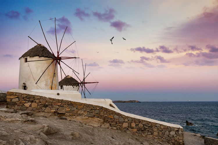View of traditional windmill by sea against sky during sunset