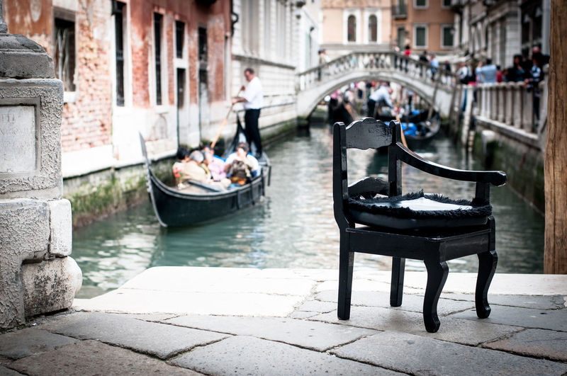 Chair on walkway against grand canal
