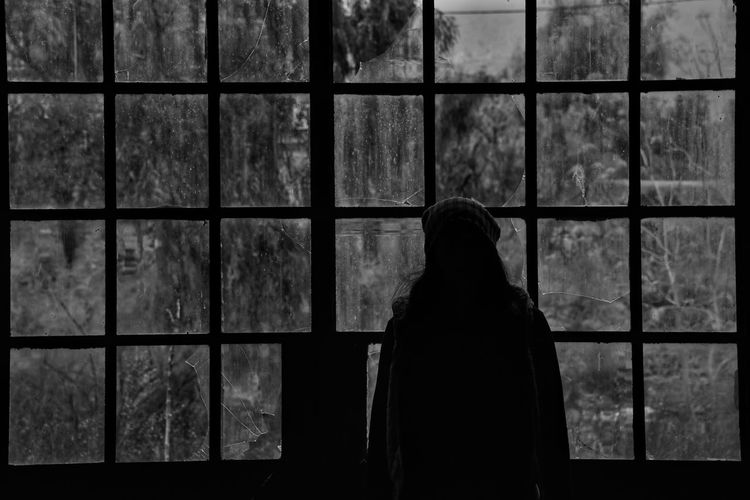 Silhouette woman standing against window