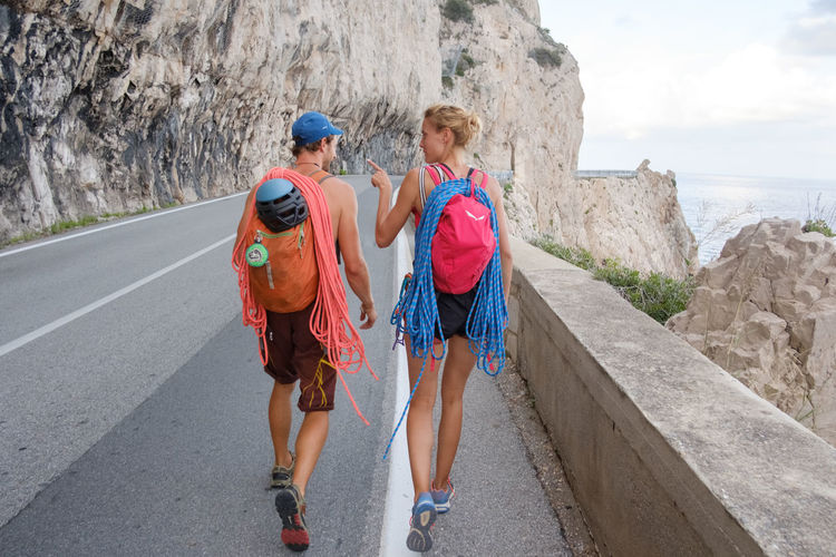 Rear view of backpackers walking on road by cliff