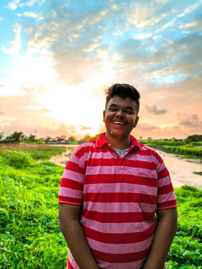 Portrait of smiling young man standing on field
