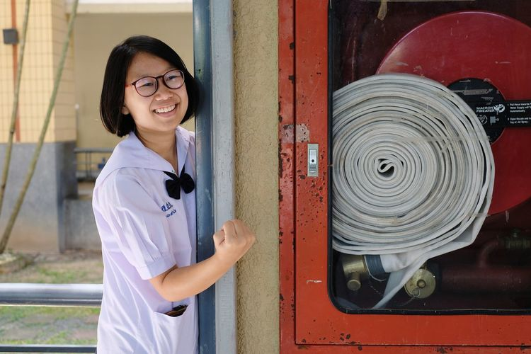 Smiling girl standing by fire hose