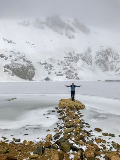 Man With Arms Outstretched Standing On Rock Against Lake During Winter