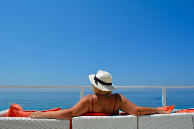 Womann relaxing on beach against clear blue sky
