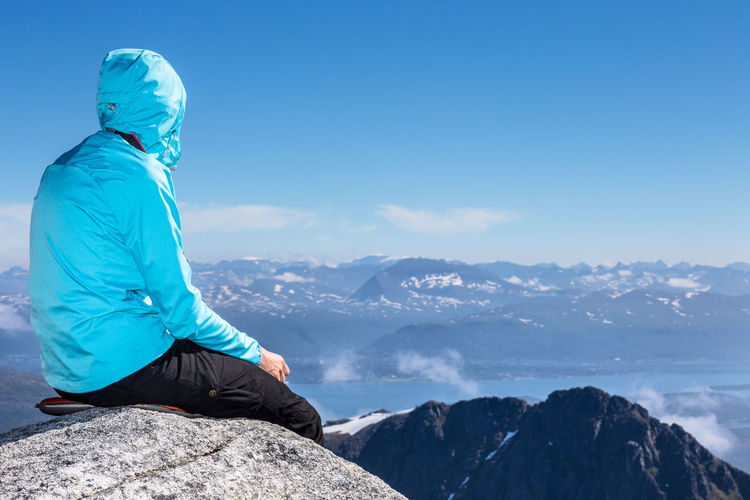 Person sitting on rock against mountains and blue sky