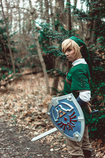Side View Of Young Man In Elf Costume With Sword And Shield Standing At Forest