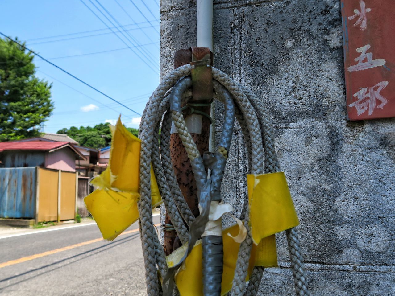 built structure, rope, day, hanging, outdoors, architecture, yellow, no people, building exterior, tied up