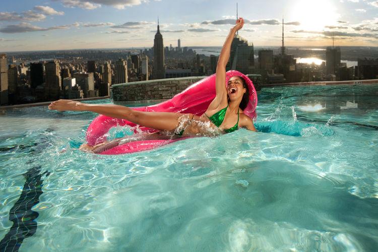 Happy bikini woman on pool raft enjoying in swimming pool