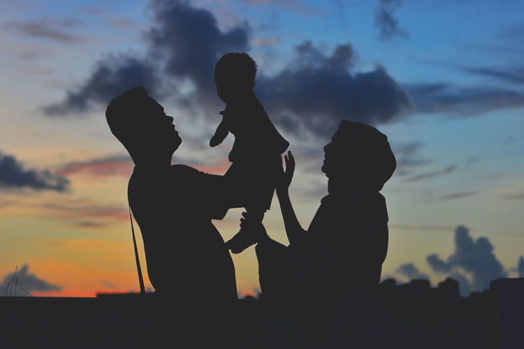 Silhouette friends with arms raised against sky during sunset