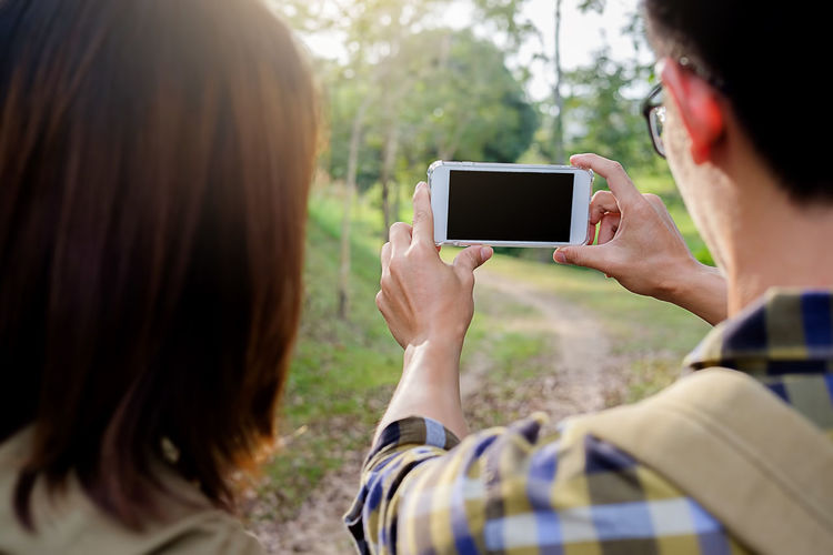 Friends photographing with mobile phone while hiking in forest