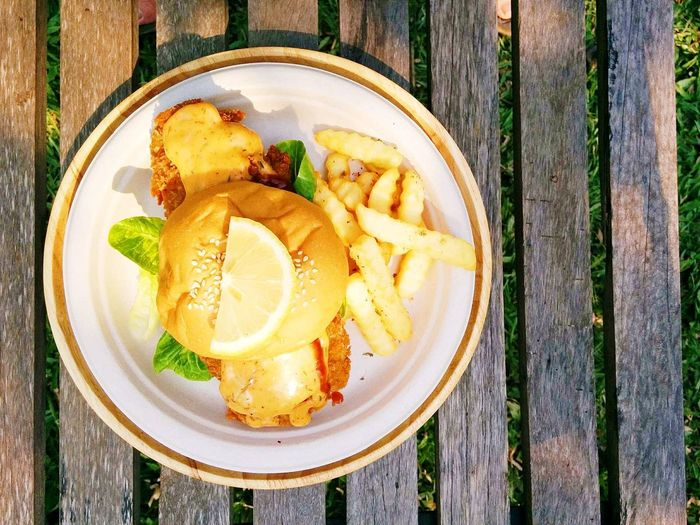 Directly above shot of fish burger with french fries served in plate on table