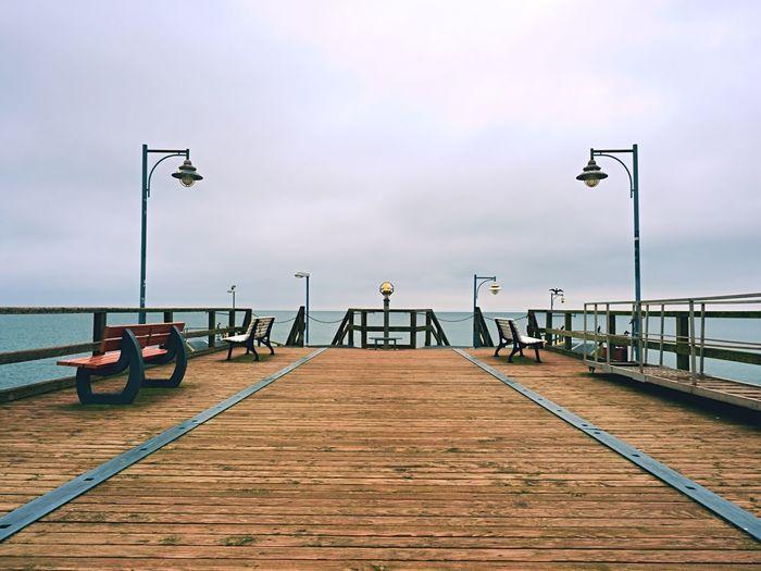 Abandoned seaside telescope . autumn misty morning on wooden pier above sea. dark atmosphere.