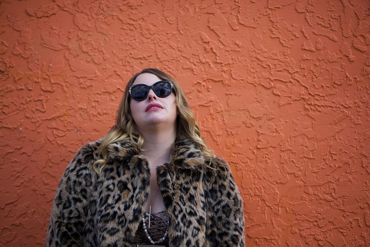 Portrait of young woman wearing sunglasses standing against brick wall