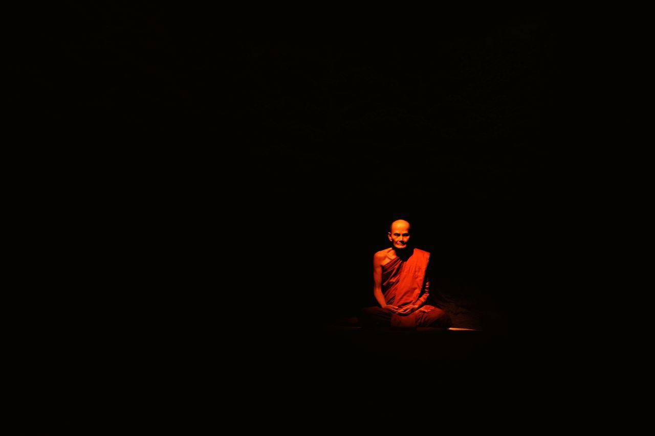 real people, copy space, one person, spirituality, men, full length, lifestyles, night, black background, sitting, indoors, one man only, adult, people