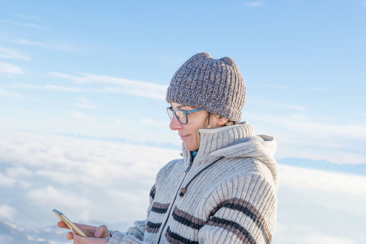 Woman using smart phone on the mountains. Panoramic view of snowcapped Alps in cold winter season. Concept of sharing life moments using new technology. Keywords: winter, phone, woman, mountain, snow, smartphone, cold, mobile, lifestyle, landscape, cell, sport, recreation, portrait, outdoors, hat, vacation, adult, season, outdoor, leisure, sunny, resort, wilderness, one person, mobile phone, sms, messaging, top, connection, smart phone, wireless technology, social networking, people, exploration, adventure, internet, snowcapped, tourist, high up, mountain range, freedom, scenics, remote, travel, panoramic, alps Beauty In Nature Communication Day Leisure Activity Lifestyles Mobile Phone Nature One Person Outdoors Portable Information Device Real People Sky Smart Phone Technology Using Phone Warm Clothing Water Wireless Technology Women Young Adult Young Women