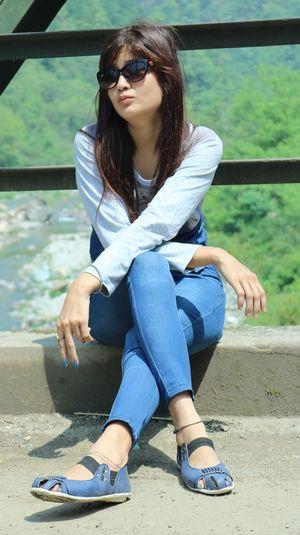 Beautiful woman sitting on bridge against railing