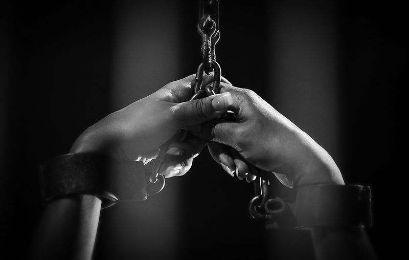Cropped hands of person with handcuffs