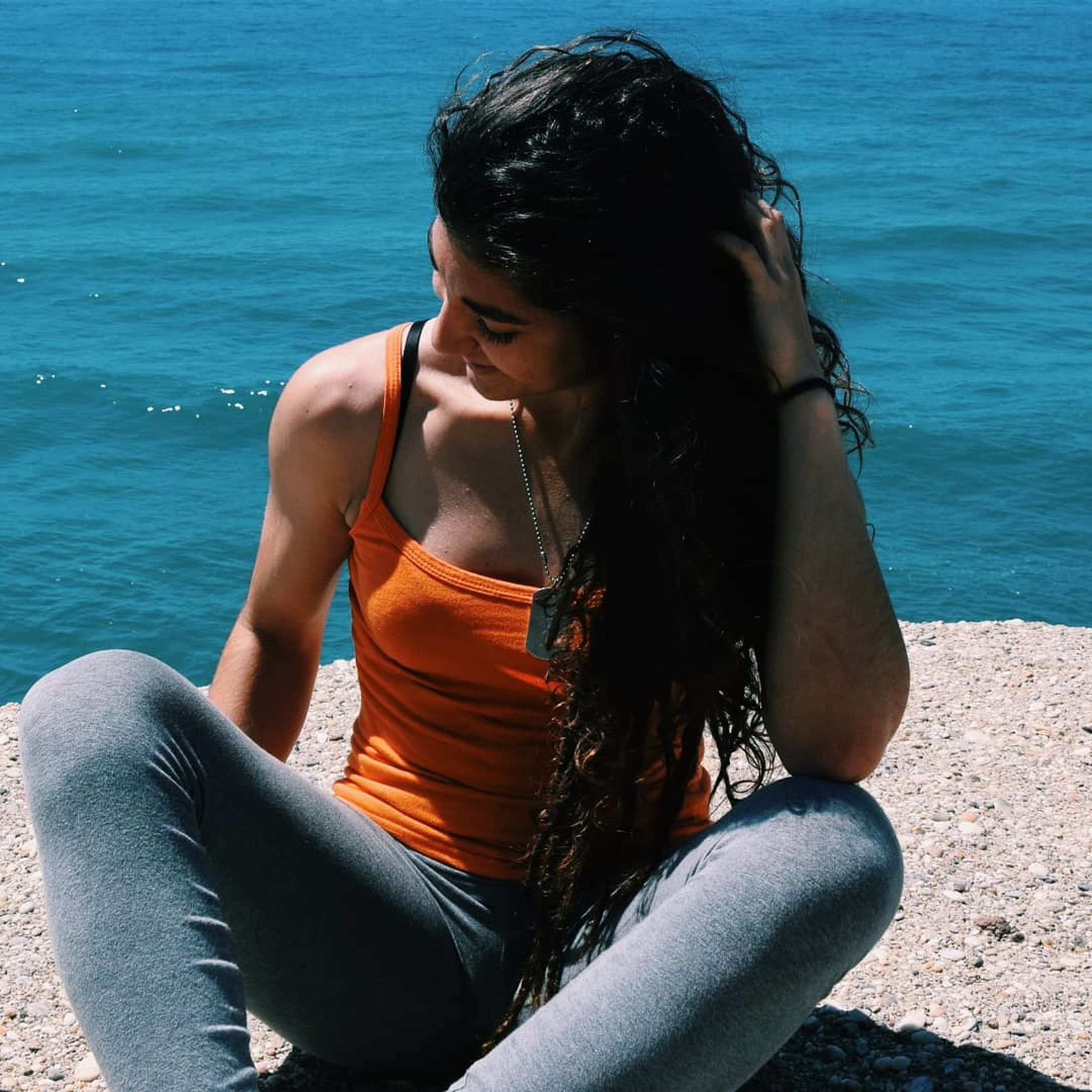 water, leisure activity, one person, sitting, lifestyles, sea, real people, three quarter length, young adult, young women, women, nature, day, sunlight, hairstyle, adult, black hair, outdoors, hair, beautiful woman
