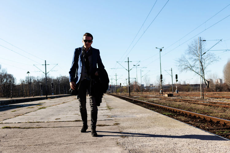 Man standing on railroad track against sky