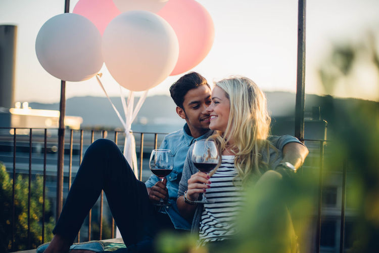 Couple Sitting With Wine By Balloons Against Sky